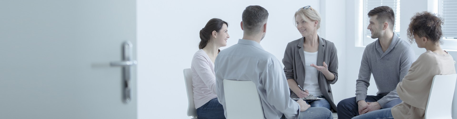 Close-up of psychotherapist listening to patient with anxiety disorder during group session